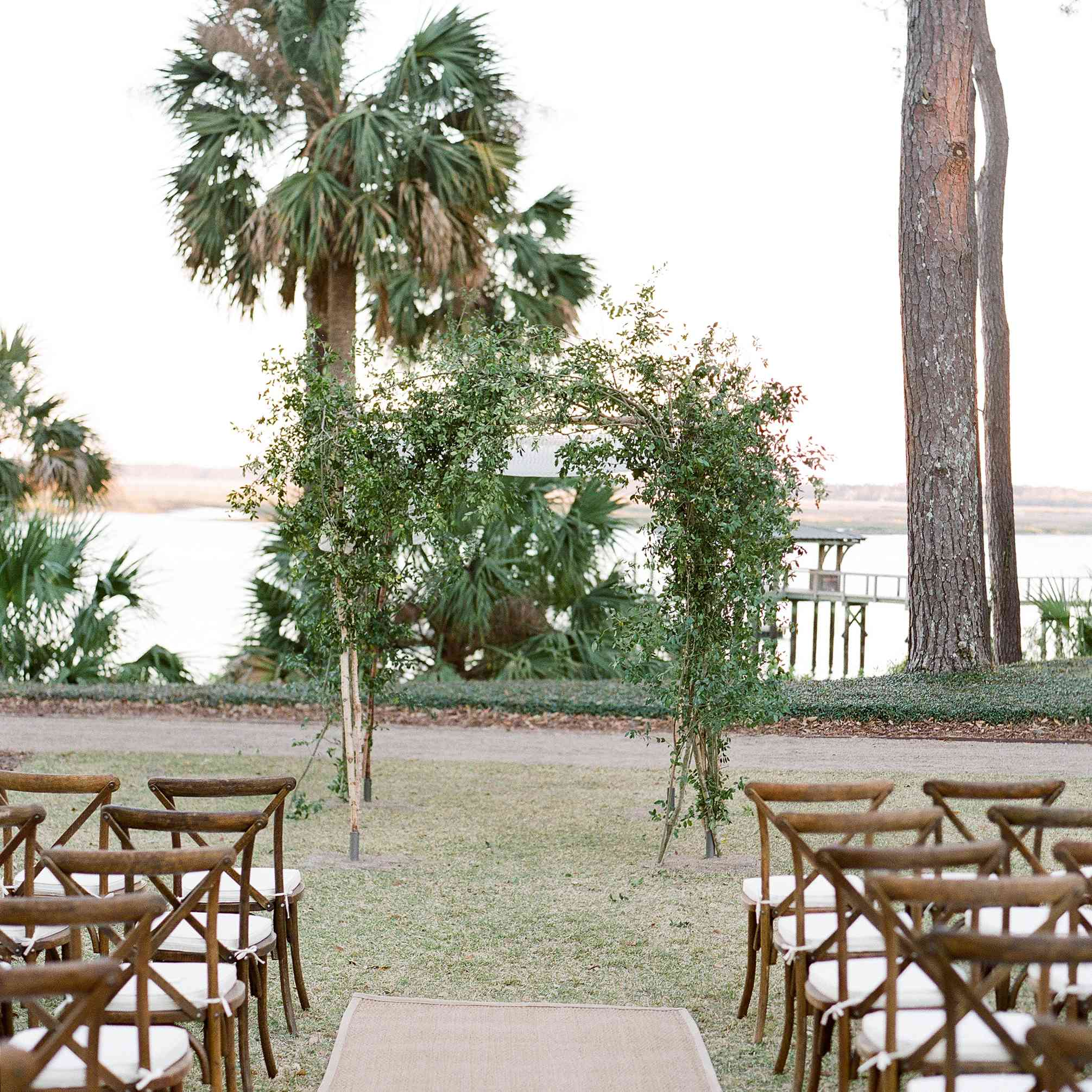 Wedding aisle with sea grass runner and branch arch