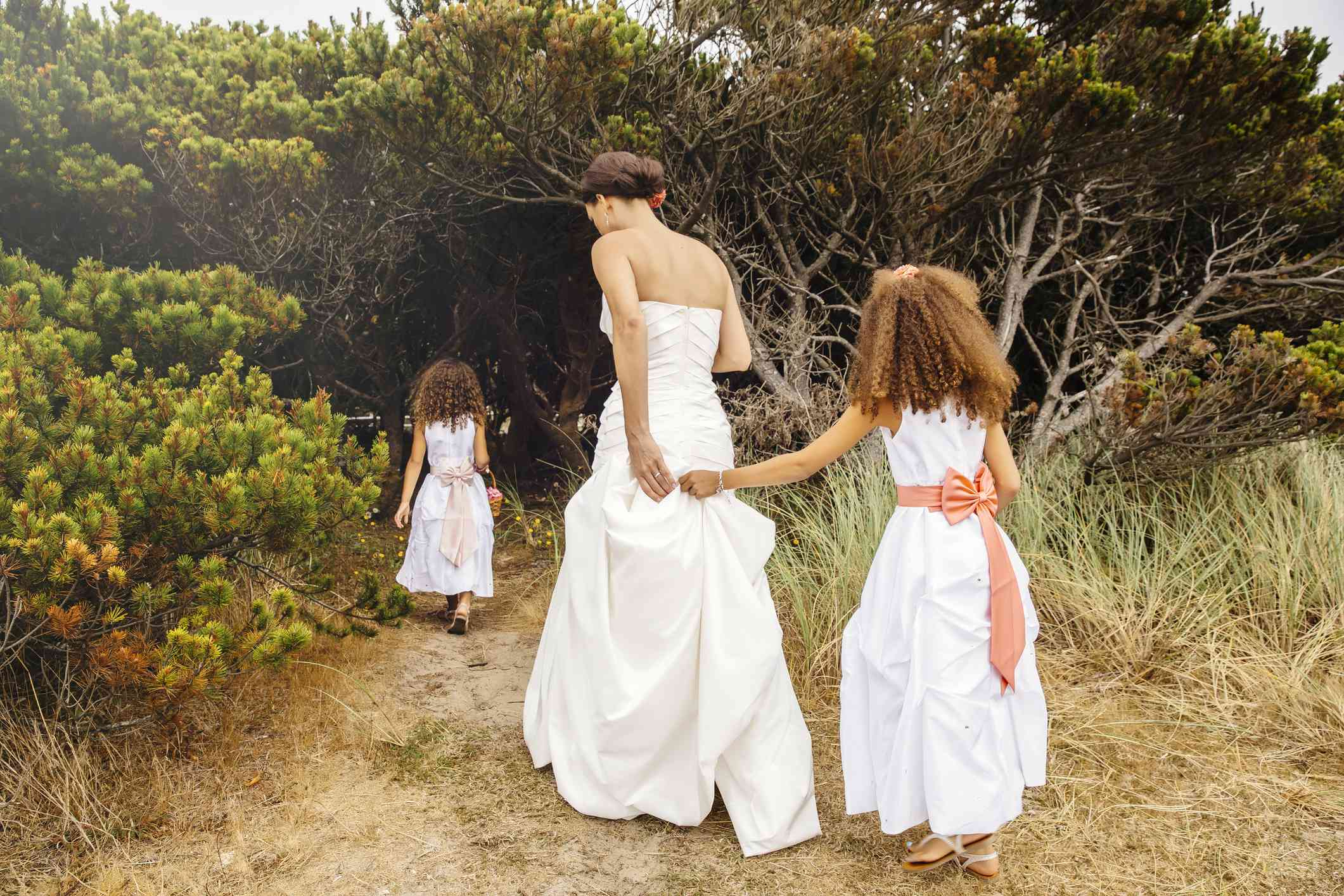 Bride walking in woods with two young flower girls