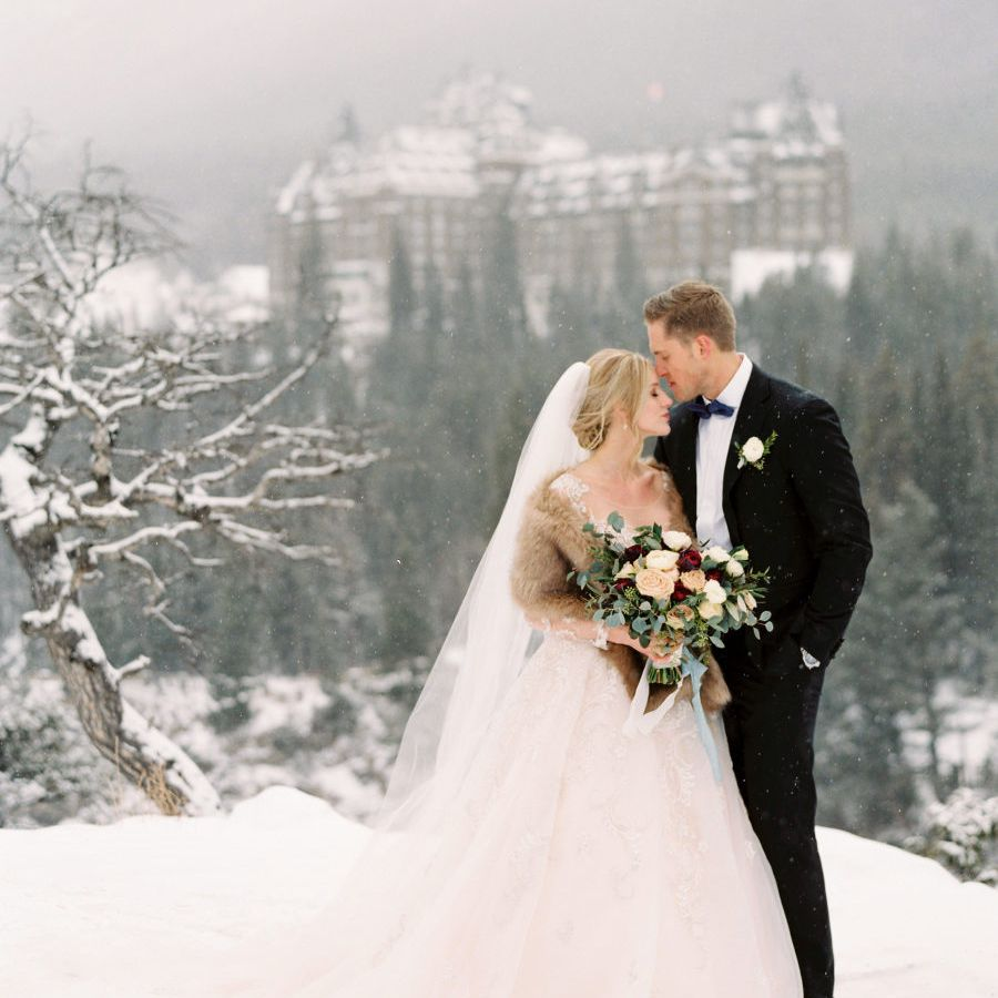 Bride and groom posing in the snow with a castle in the background
