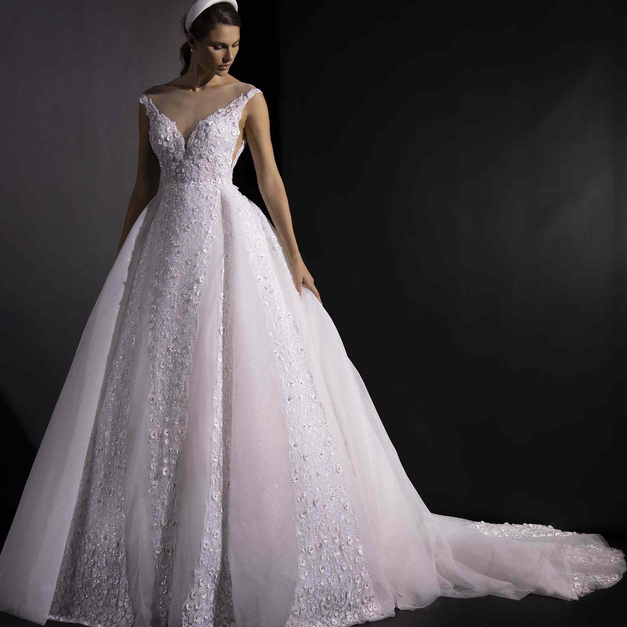 Model in floral lace embellished ballgown with an illusion neckline