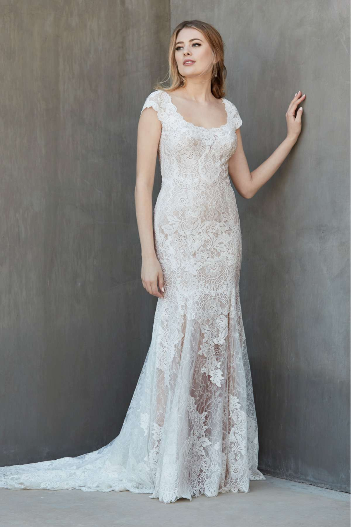 Model in allover lace fit and flare gown with a scoop neckline and cap sleeves