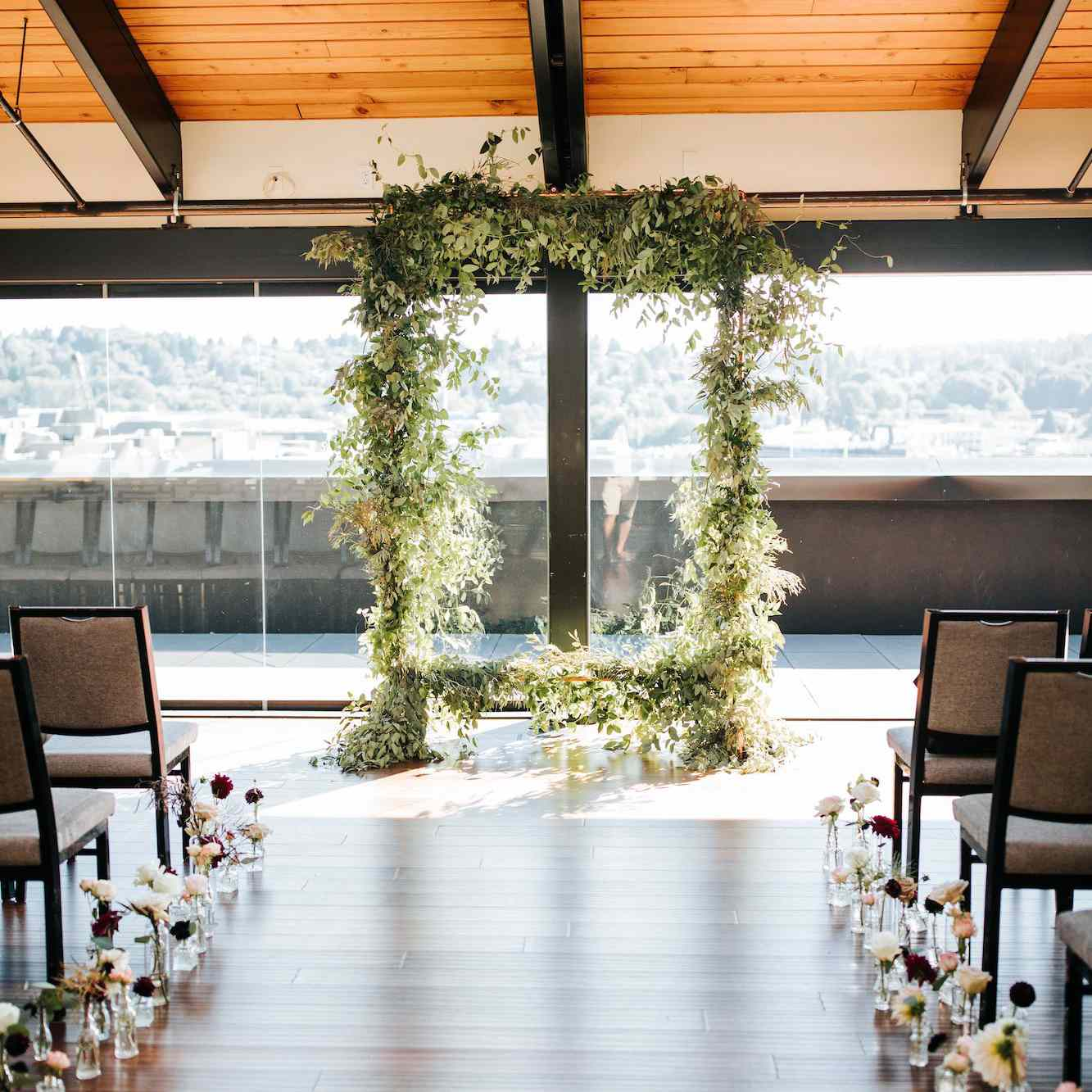 An indoor ceremony with glass vases of roses lining the aisle and a leafy, rectangular ceremony arch