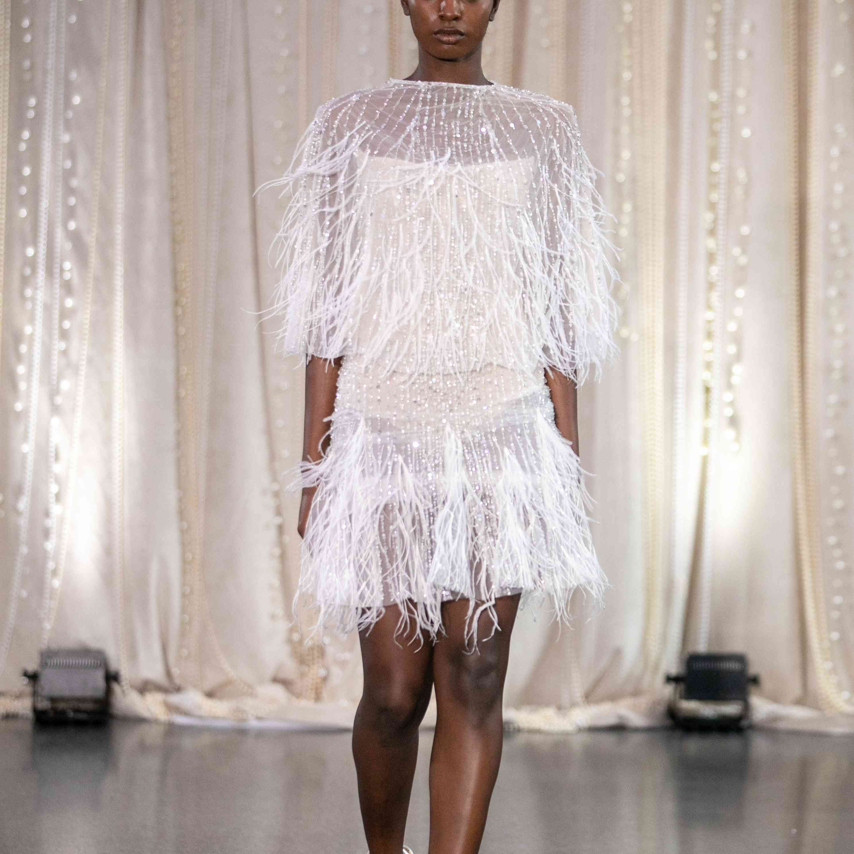 Model in mini wedding dress with feathers