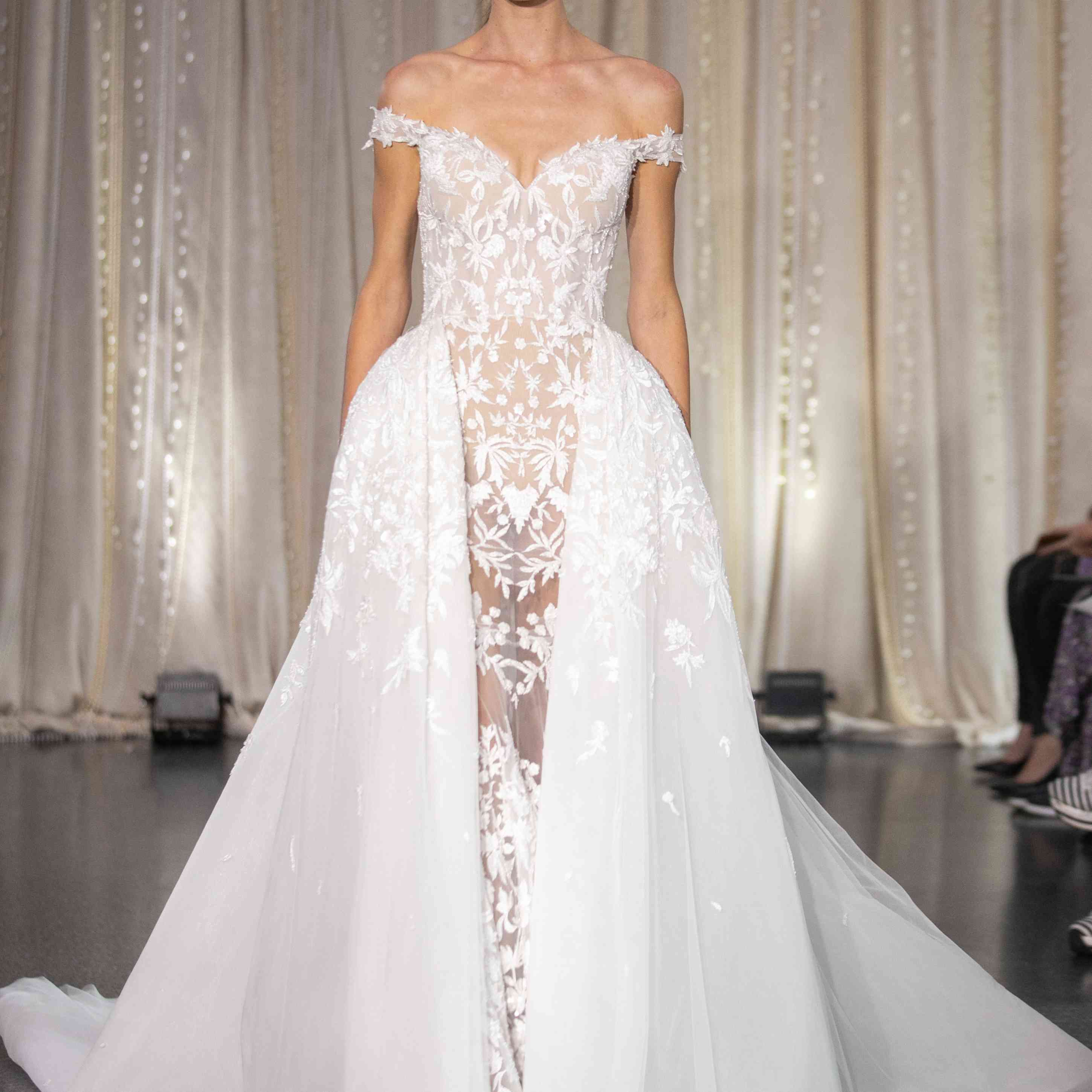 Model in off-the-shoulder wedding dress with overskirt