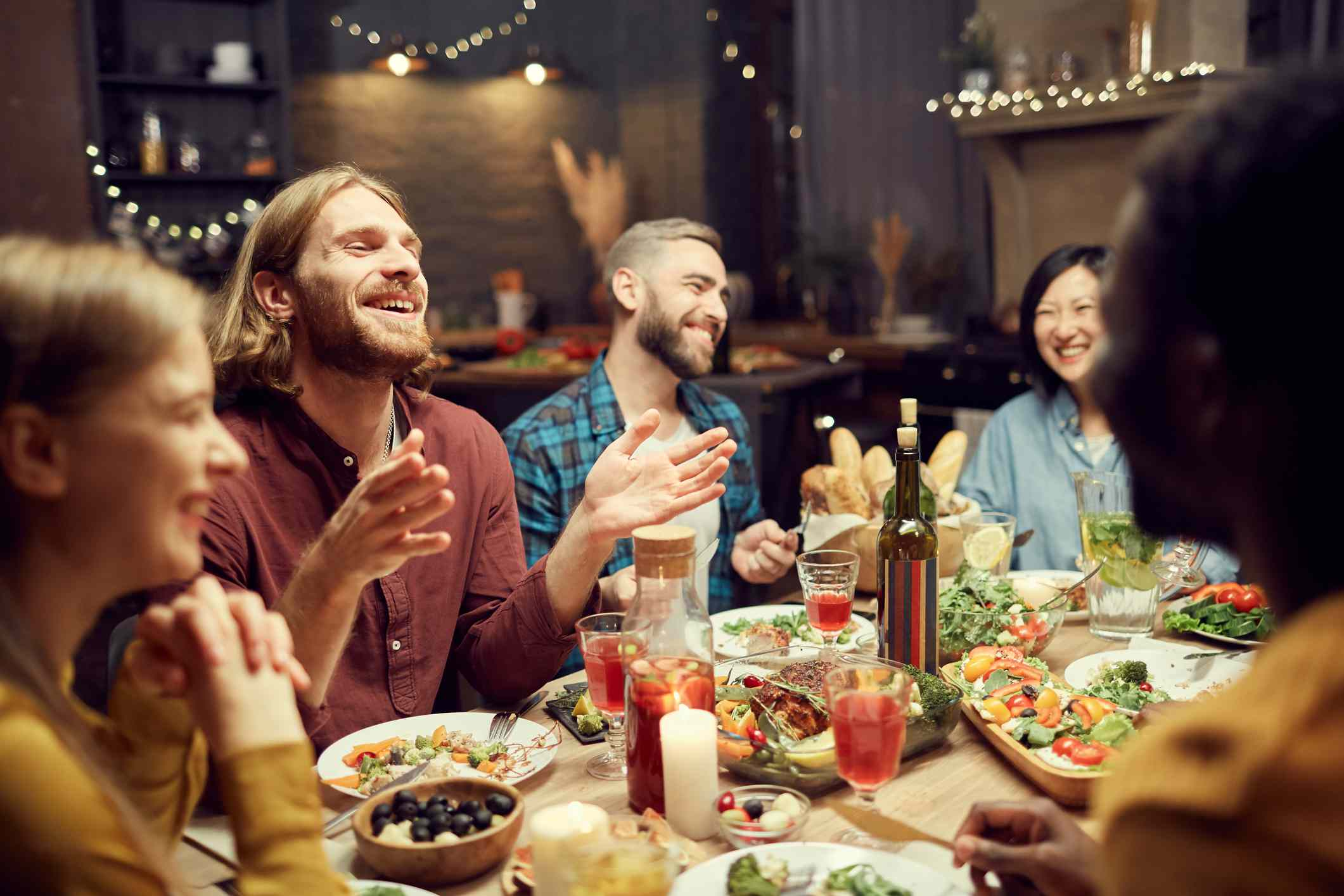 Friends laughing and having dinner together