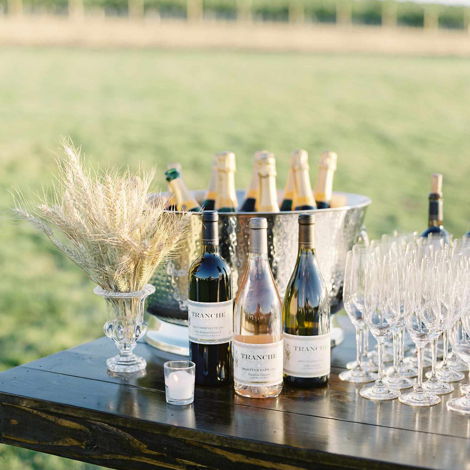 Bottles of wine and glasses on a table with a vineyard in the background
