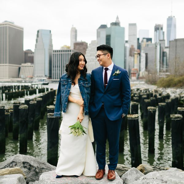 Bride and groom stand next to river
