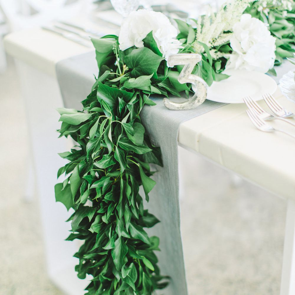 tablescape with garlands of greenery and white peonies and hydrangeas