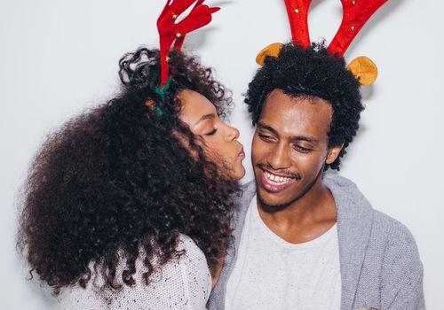 playful couple wearing reindeer headbands