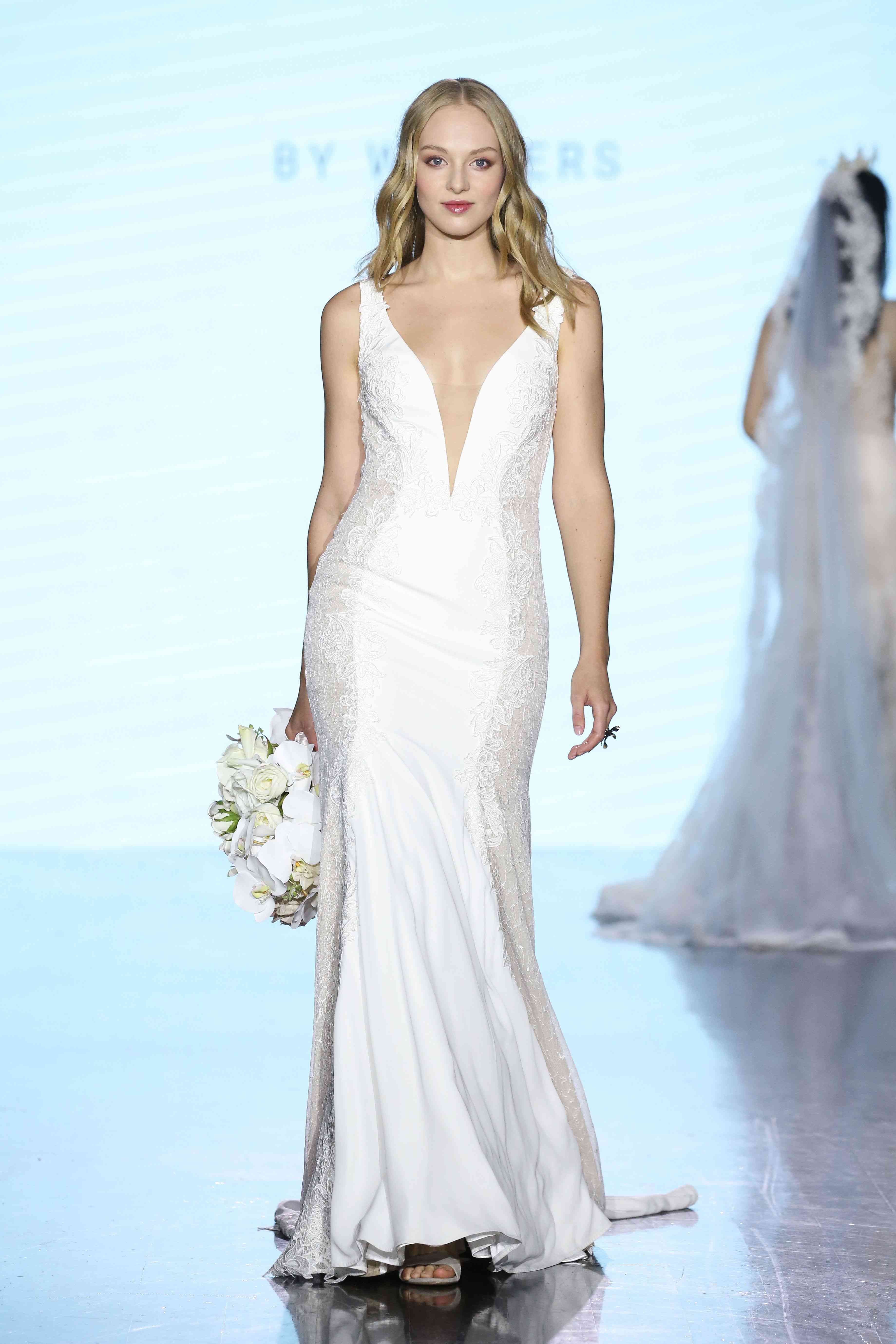 Model in lace-paneled fit-and-flare gown with plunging illusion neckline