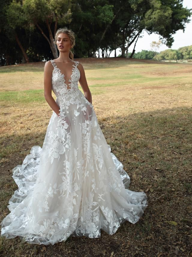 Model in deep V all-over lace bridal gown with pockets