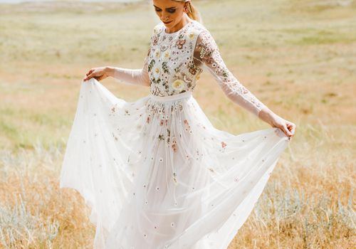 <p>Bride holding skirt in field</p>