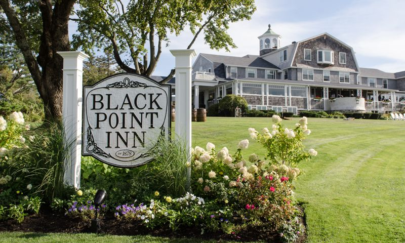 Welcome sign of Black Point Inn with inn in the background
