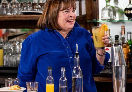 Ina Garten smiling behind a bar holding an orange beverage