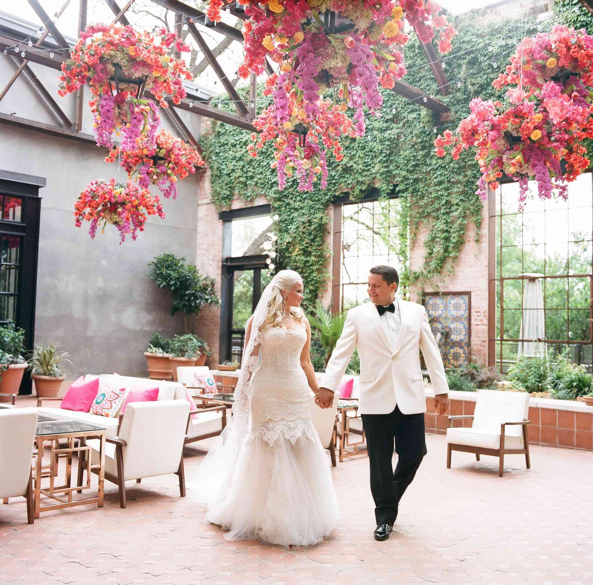 Couple holding hands walking through a floral-filled venue on their wedding day