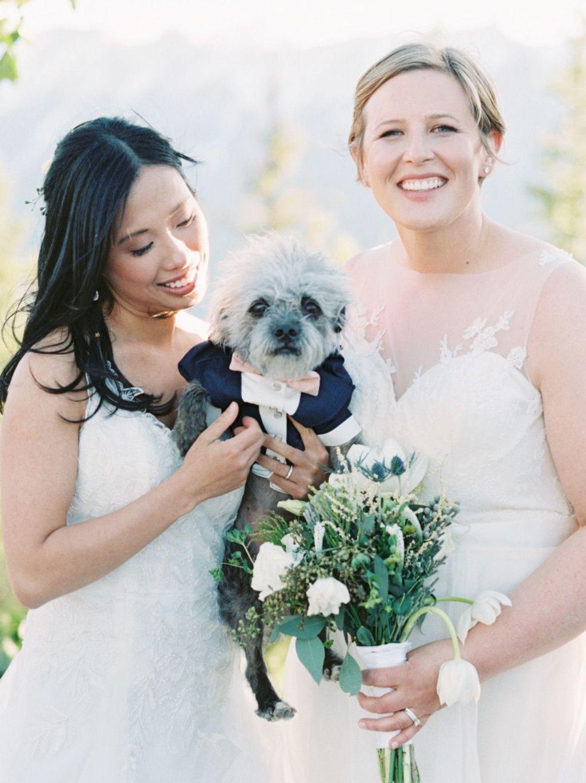 Brides holding puppy in blue tux