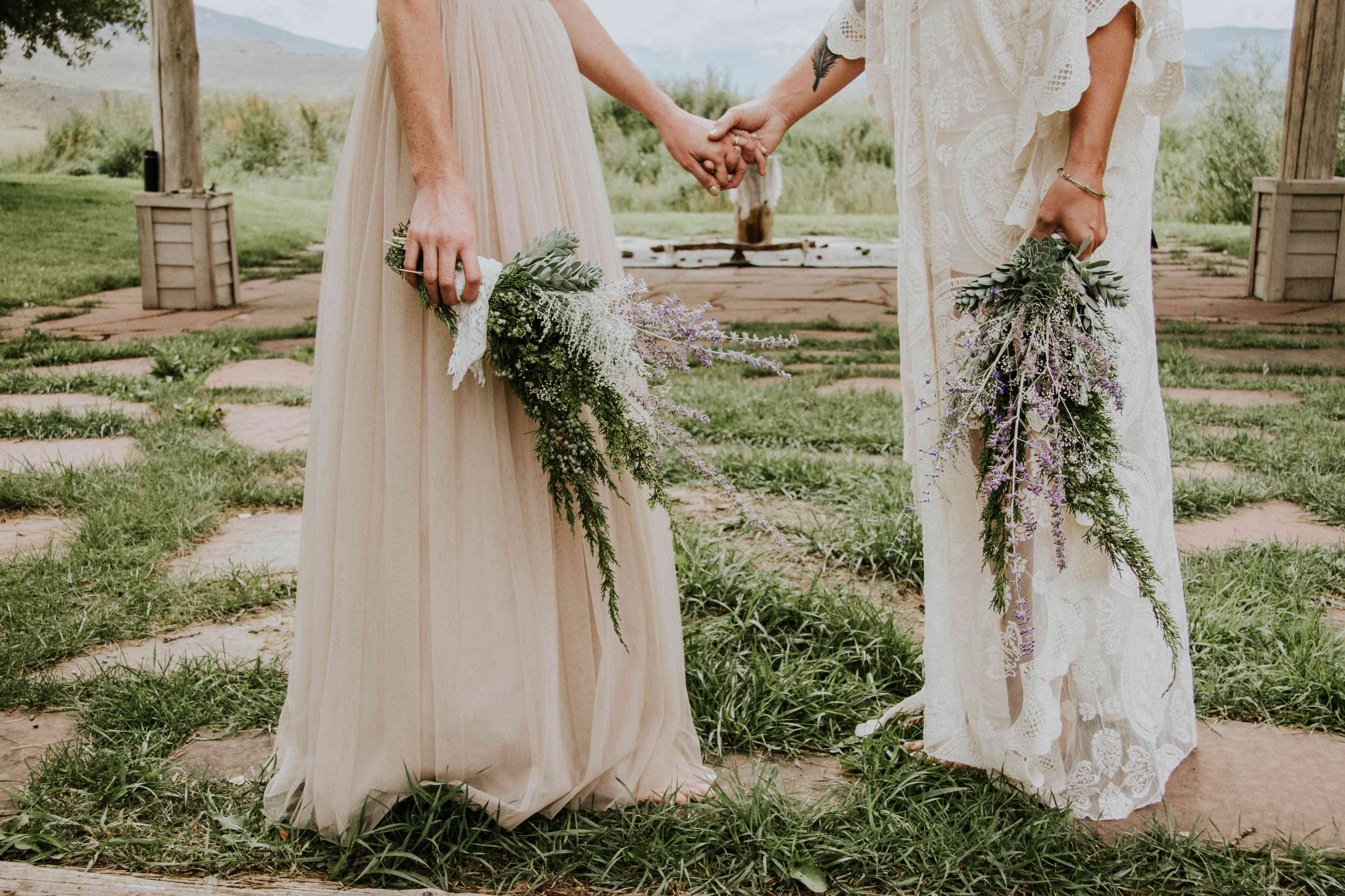Brides holding hands and bouquets