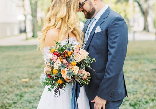 bride and groom with fall bouquet