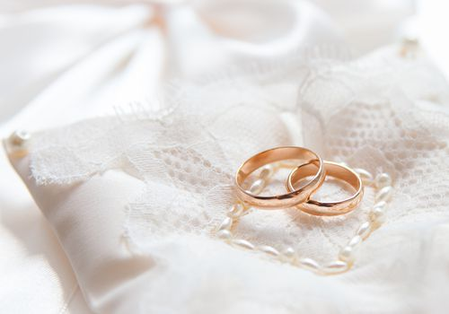 Two gold wedding rings on lace pillow