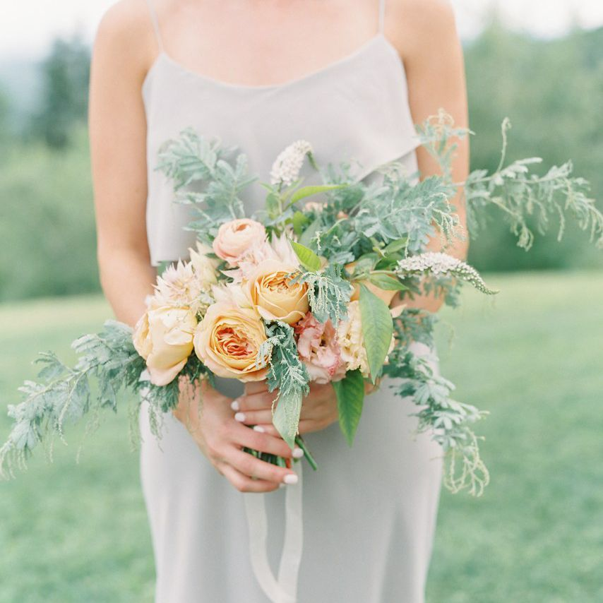 Bridesmaid holding a bouquet of peach roses and greens