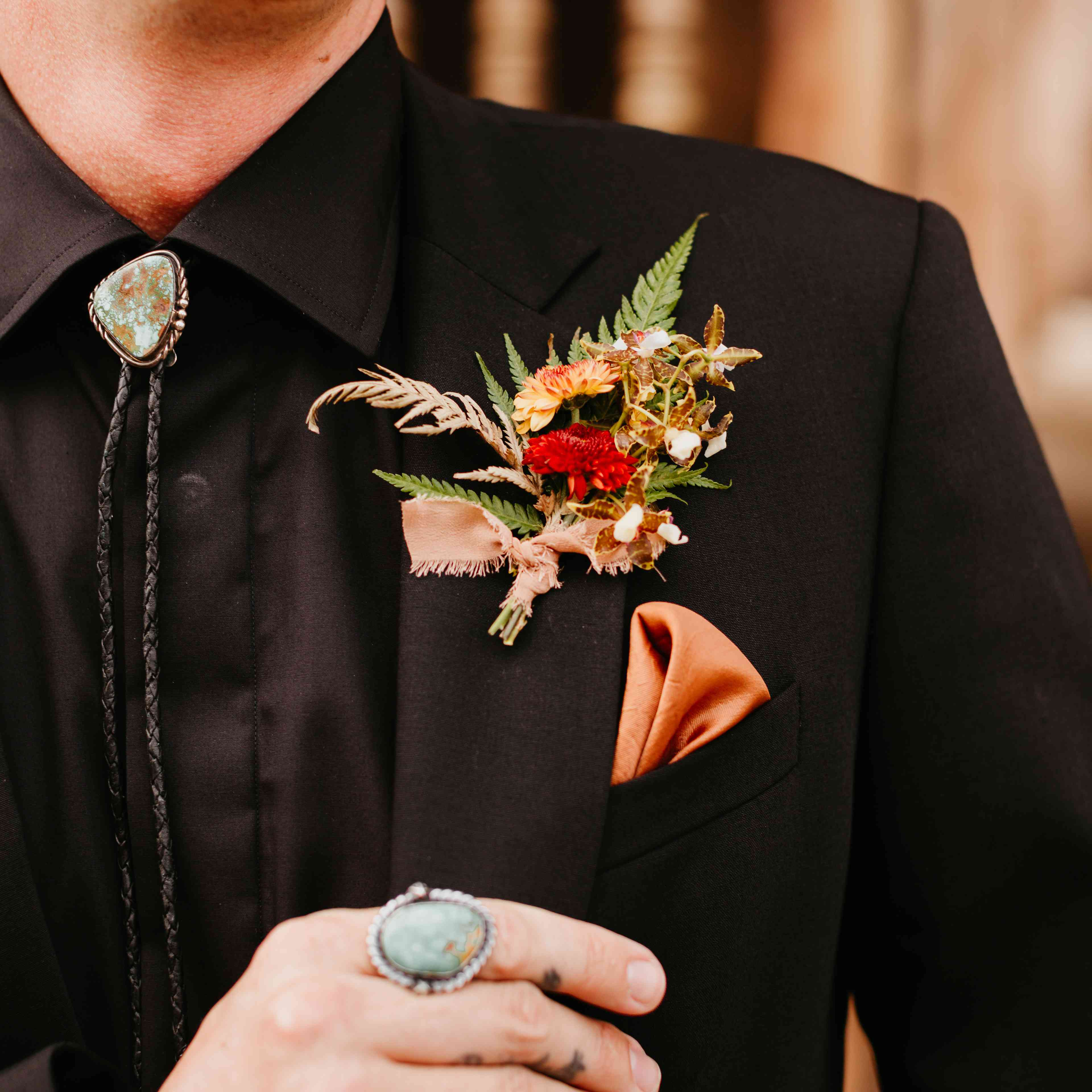 Boutonniere of rust hued mums, dried grasses, an garden clippingsd
