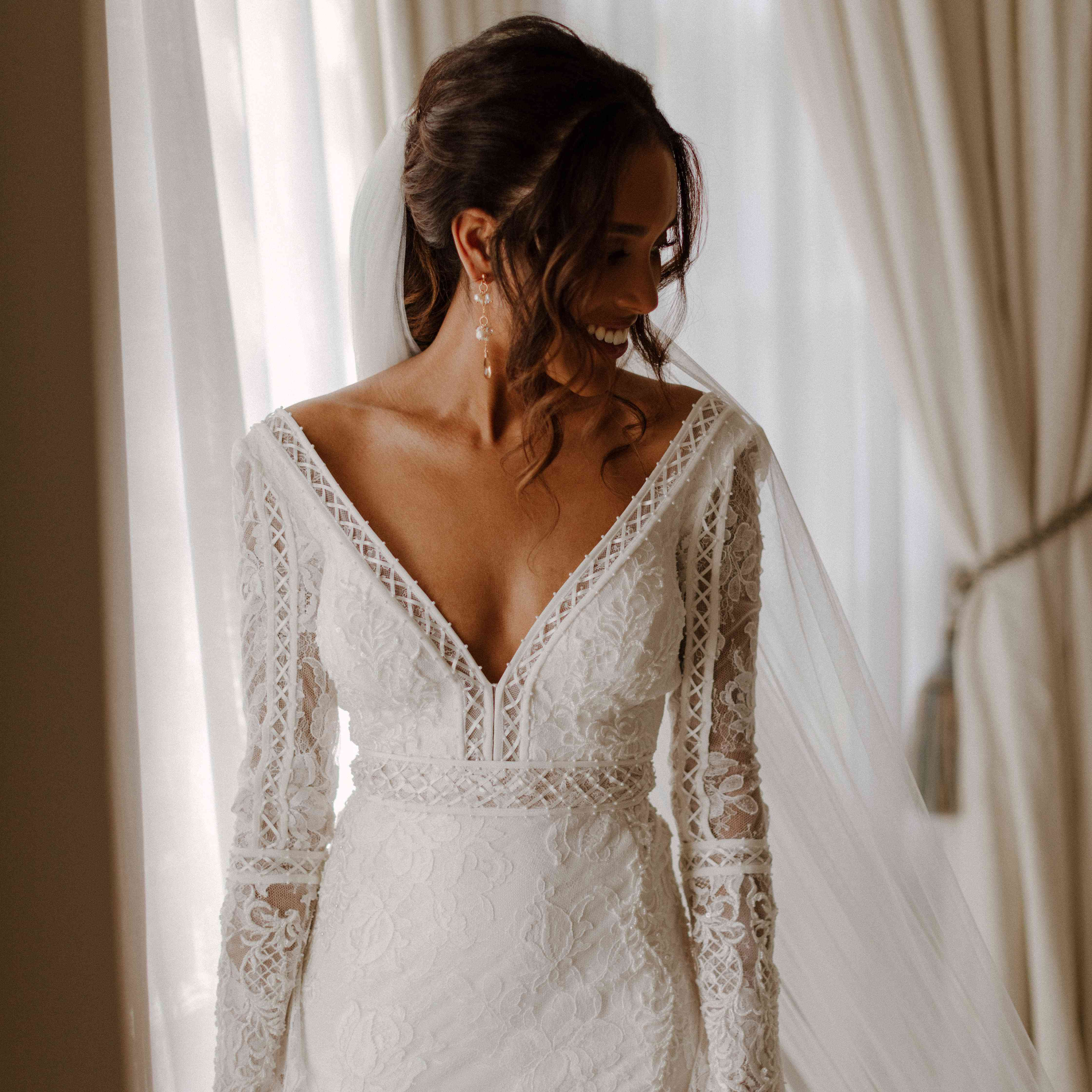 bride in long sleeve dress with veil