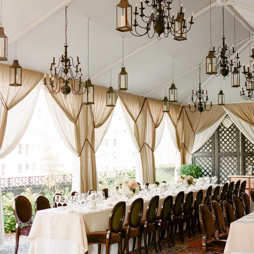Intimate wedding reception with layered rugs, drapery, and chandeliers