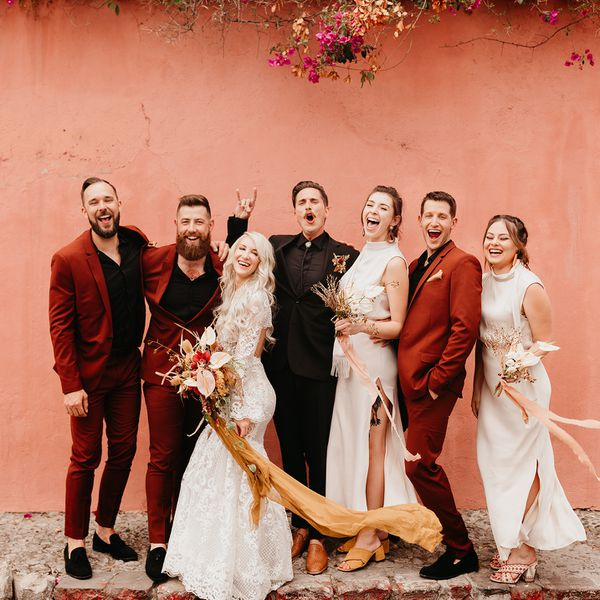 Bride and groom posing with wedding party
