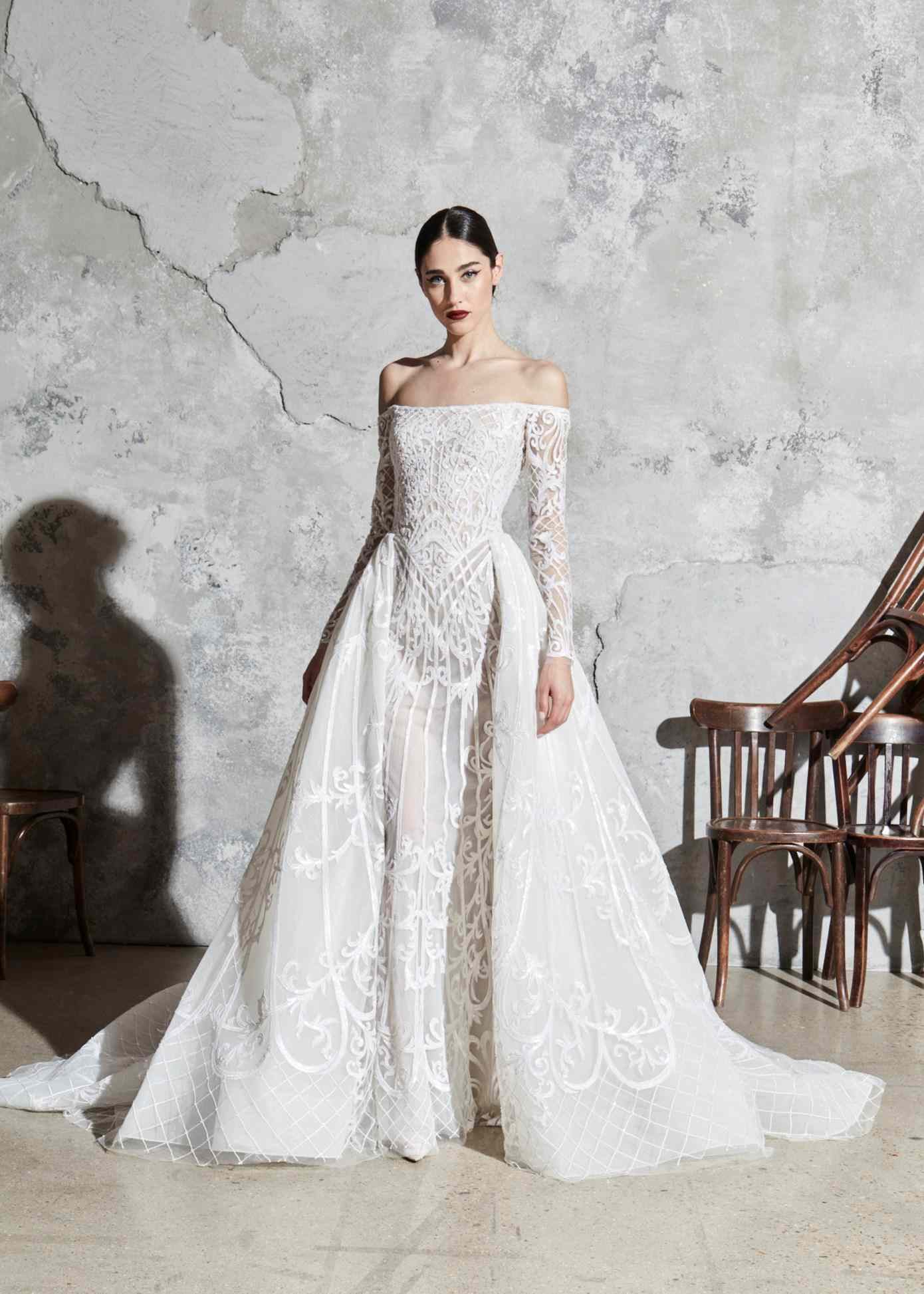 Model in off-the-shoulder embroidered gown with an attached embroidered overskirt