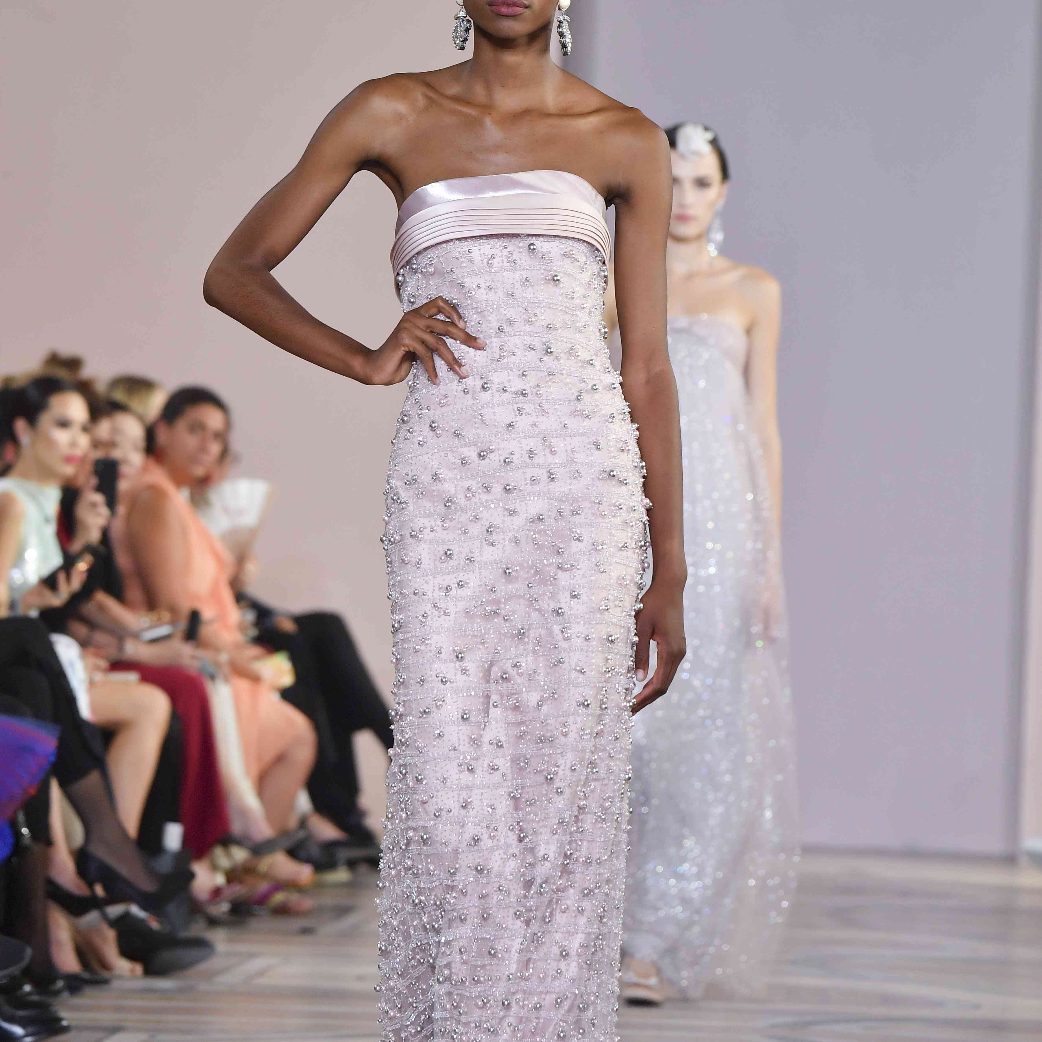 A model walks the runway in a strapless, floral embroidered, lavender gown