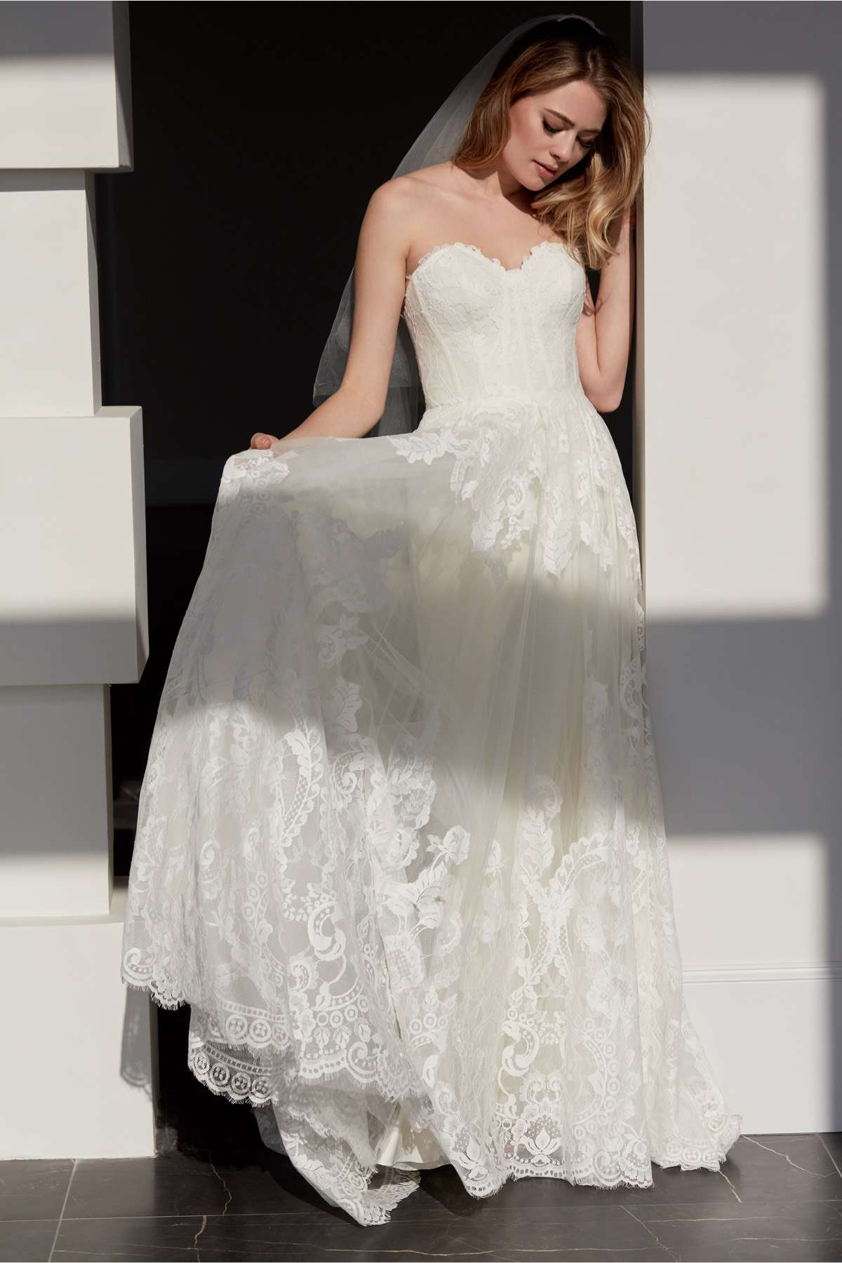 Model in strapless allover lace wedding gown