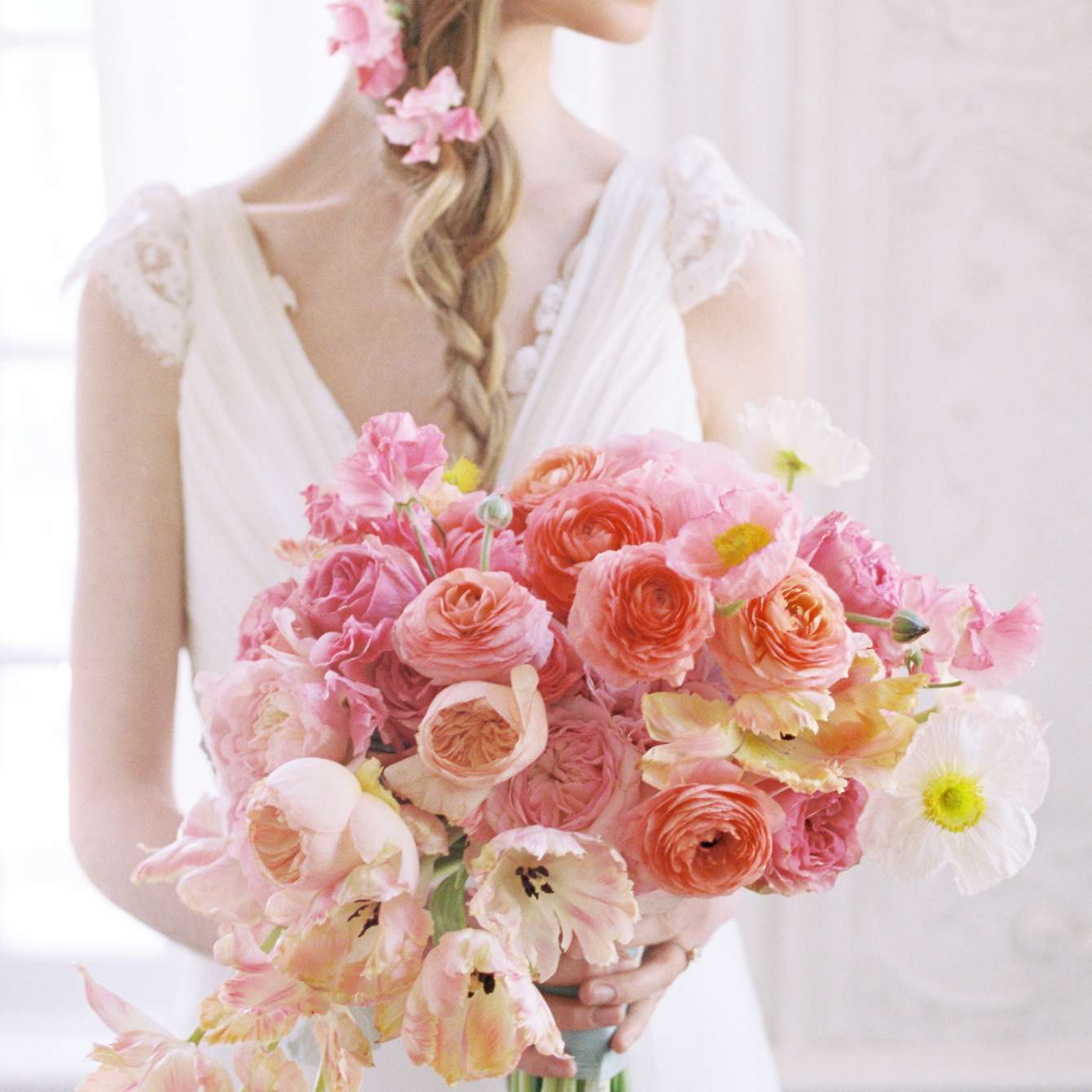 Bride holding a bouquet of parrot tulips, garden roses, ranunculus, poppies, and tweedia in shades of pink and orange