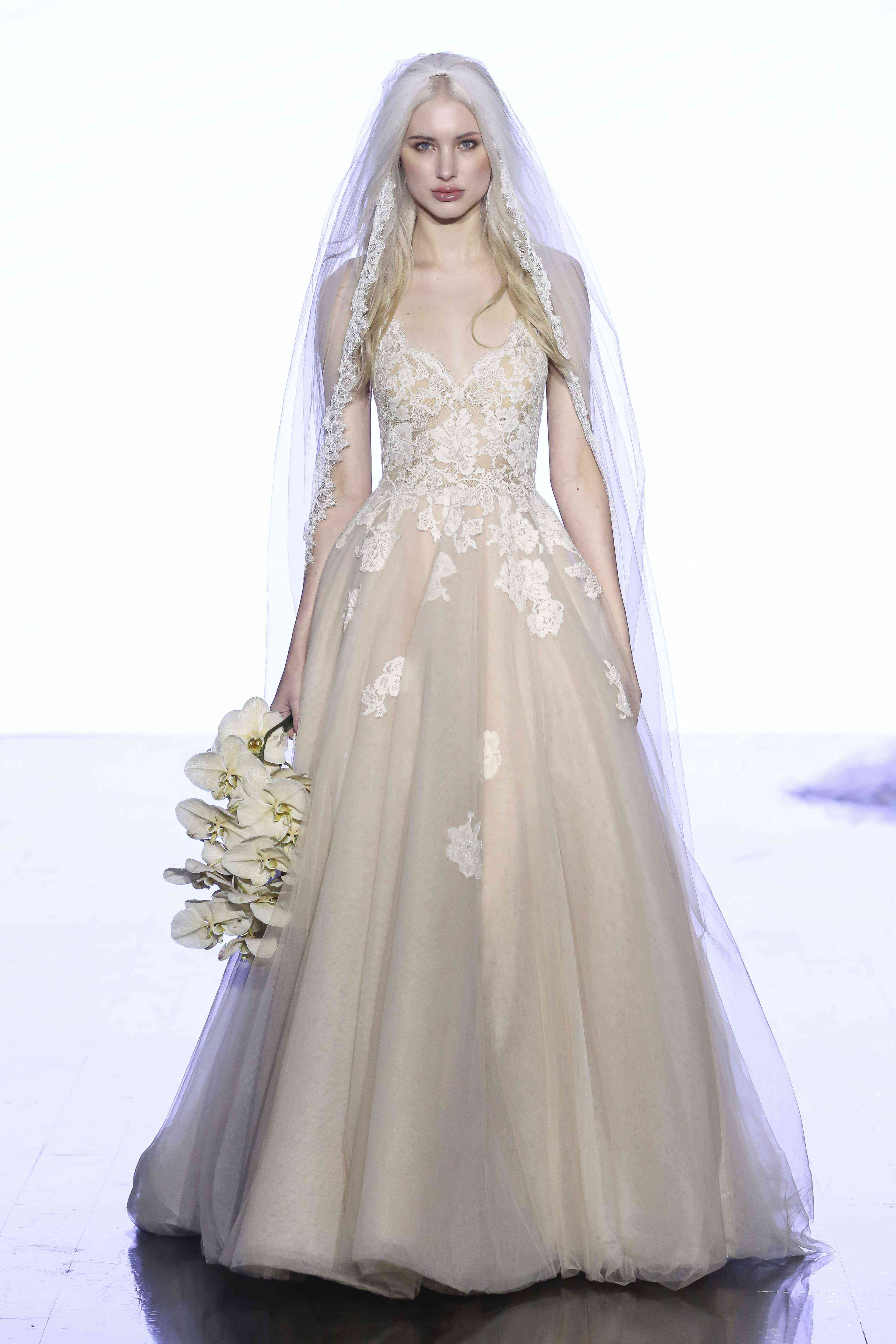 Model in off-white ballgown with a tulle skirt and a lace V-neck bodice