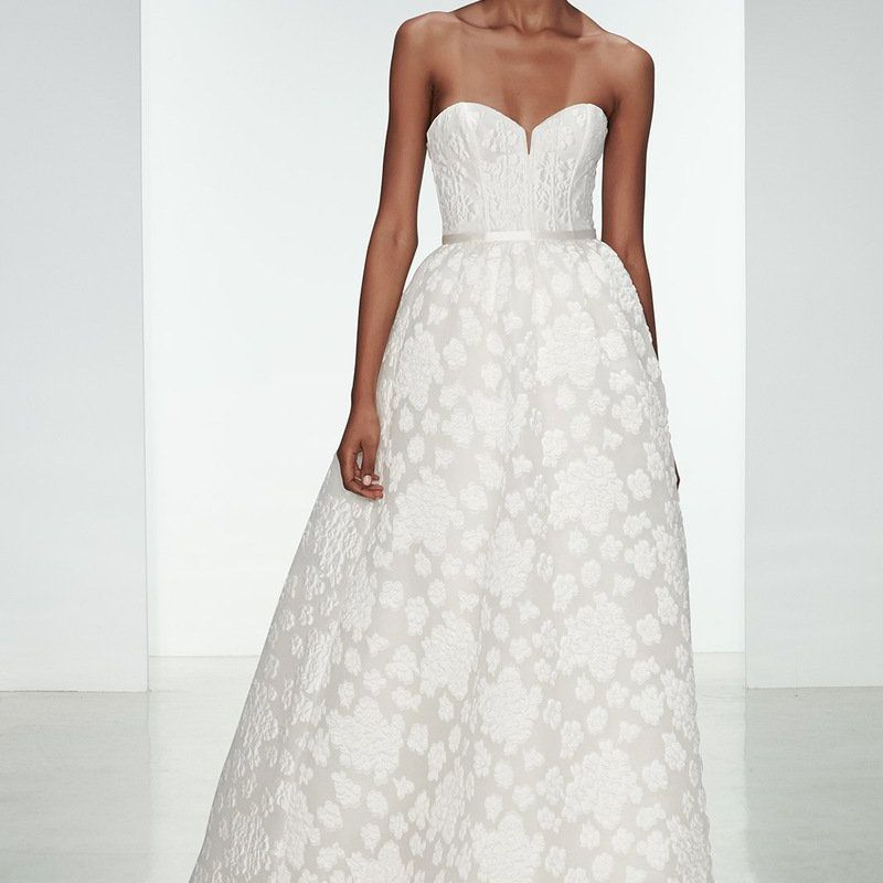Model in strapless wedding ball gown with floral embroidered skirt