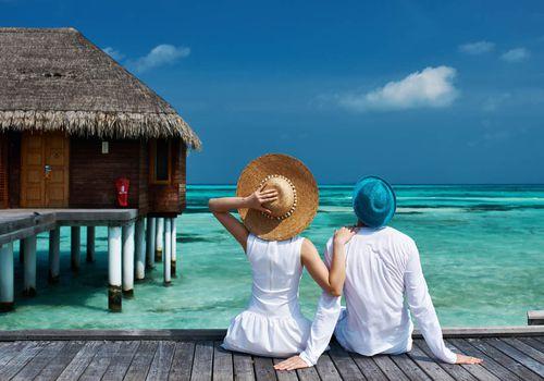 Honeymoon Couple sitting on dock near Luxury Honeymoon Hotel