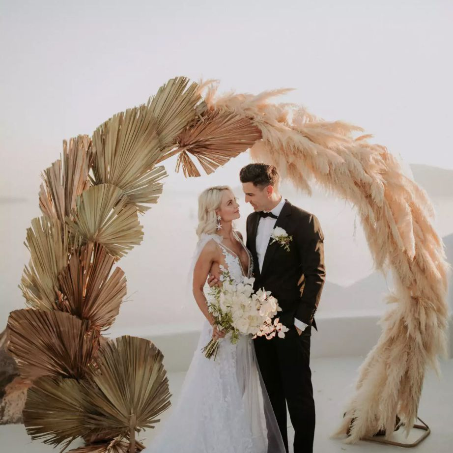 Newlyweds standing in front of circular wedding arch of dried pampas grasses and palm fronds