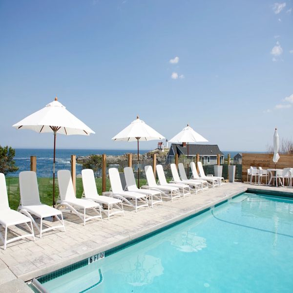 Lakefront pool with white beach chairs on a sunny day
