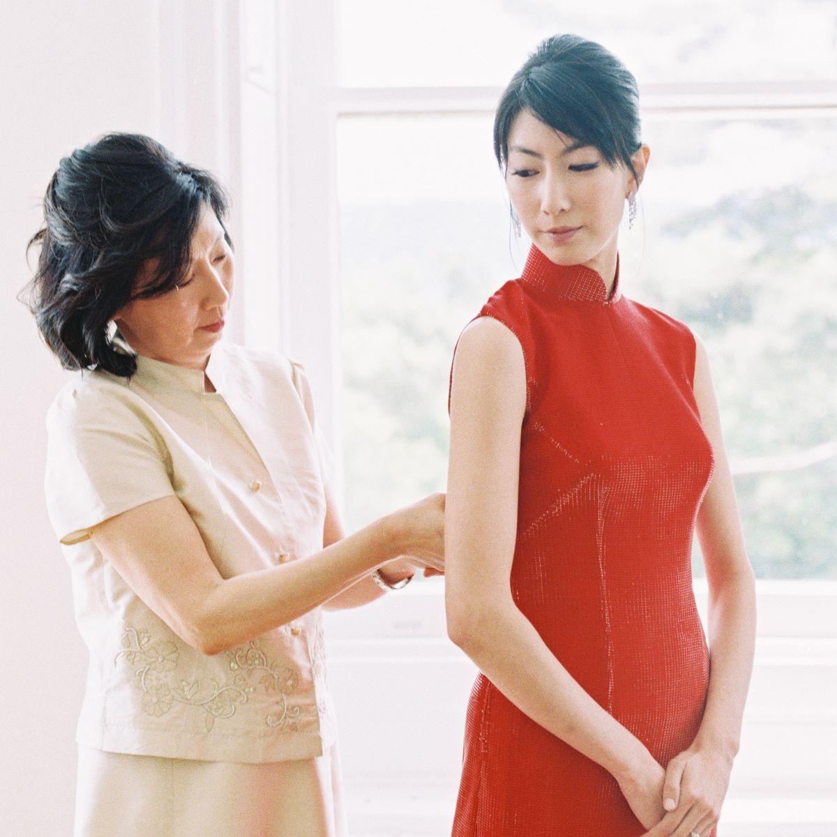 Mom zipping bride into red dress