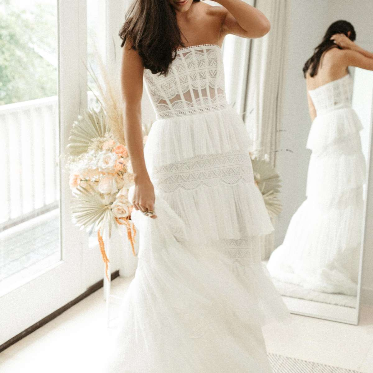 Model in strapless border lace gown with tiers of pleated netting