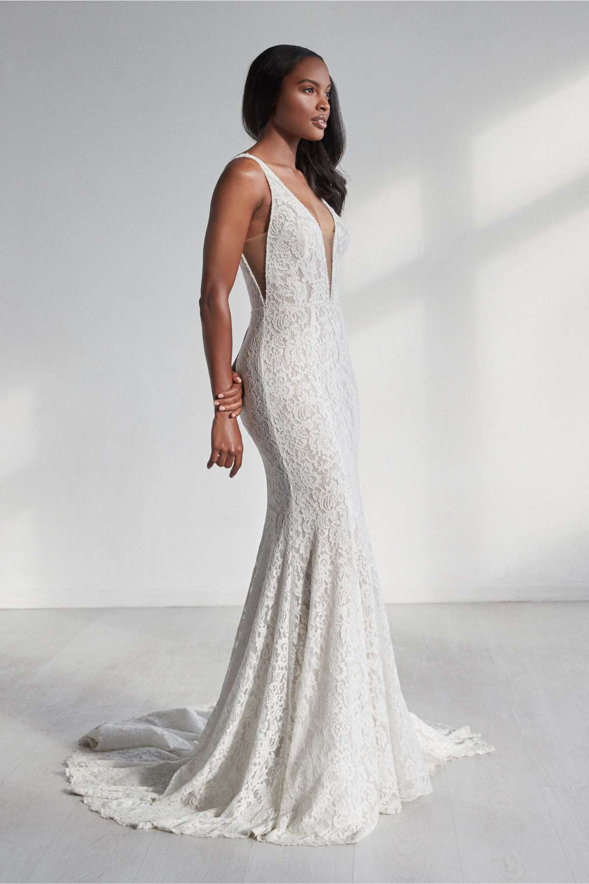 Model in sleeveless allover lace fit and flare gown with a plunging illusion neckline