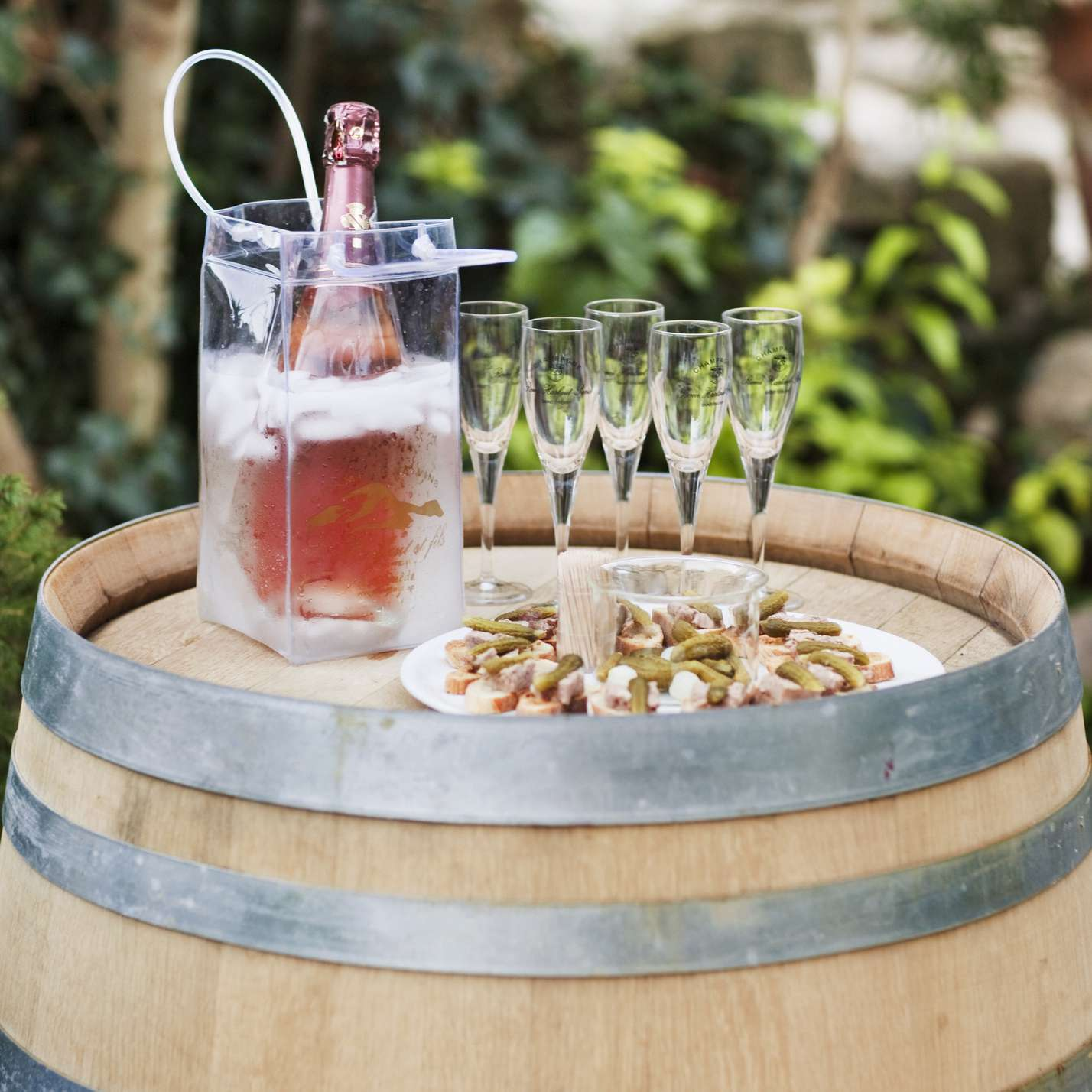 Barrell with sparking rosé wine in an ice bucket, champagne flutes, and finger food