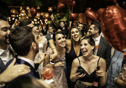 Groom and wedding guests laughing during party