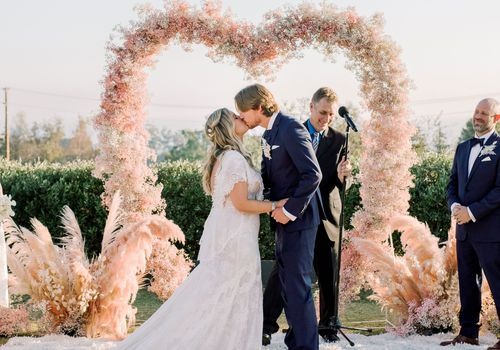 Bride and groom kissing at a floral flower-shaped altar