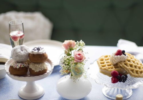 Donuts, waffles and champagne with fruit sit at a wedding head table decorated delicately with small flowers and baby's breath.