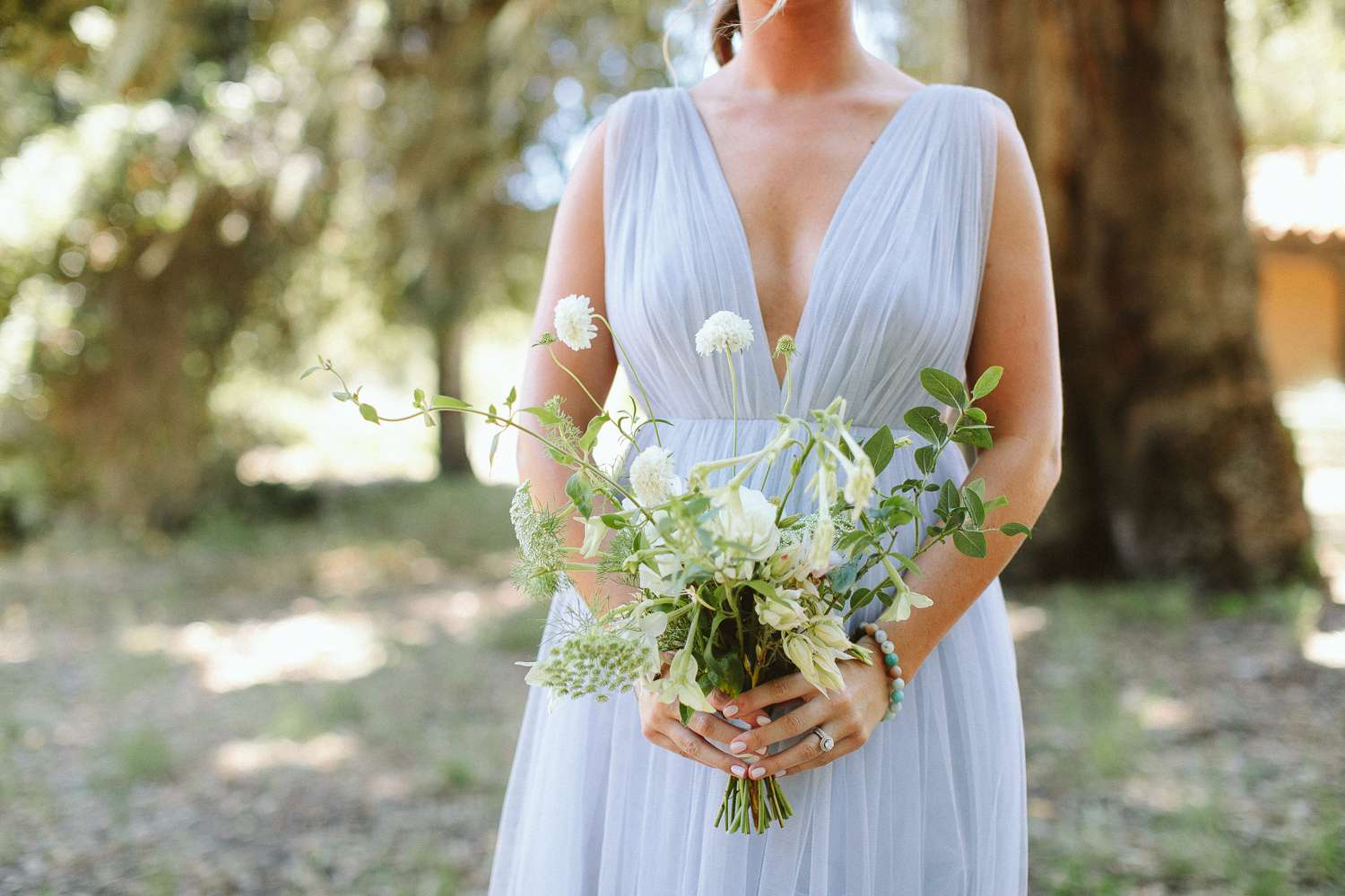 Bridesmaid holding white bouquet of queen anne's lace and cosmos