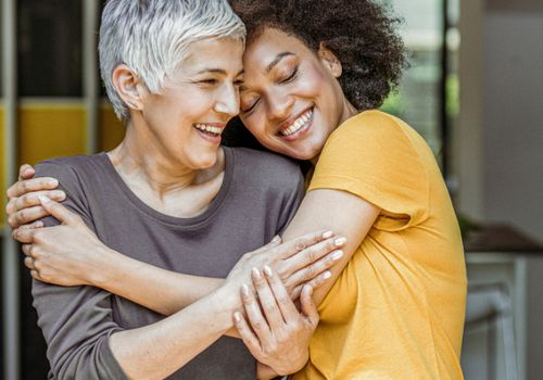 Young woman hugging older woman, both are smiling