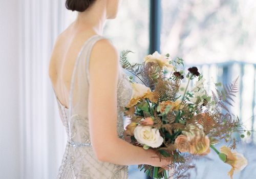bride wearing vintage wedding gown holding her bouquet