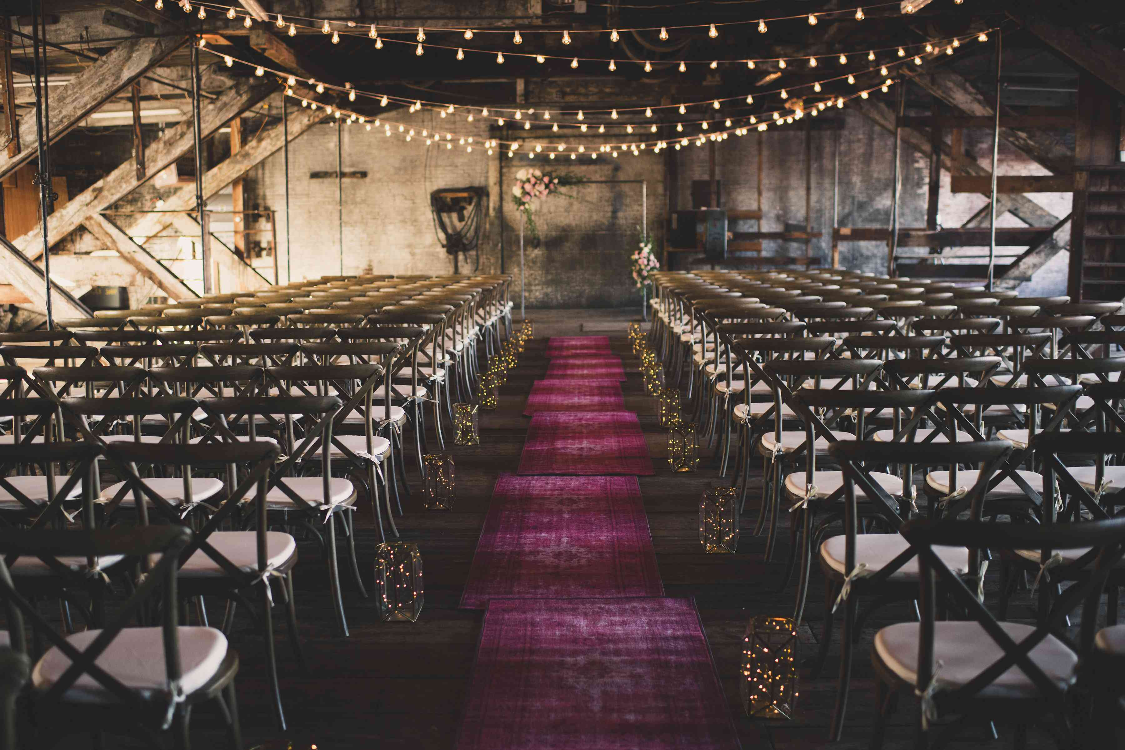 Indoor wedding aisle with red rugs as a runner, lined with jars of fairy lights