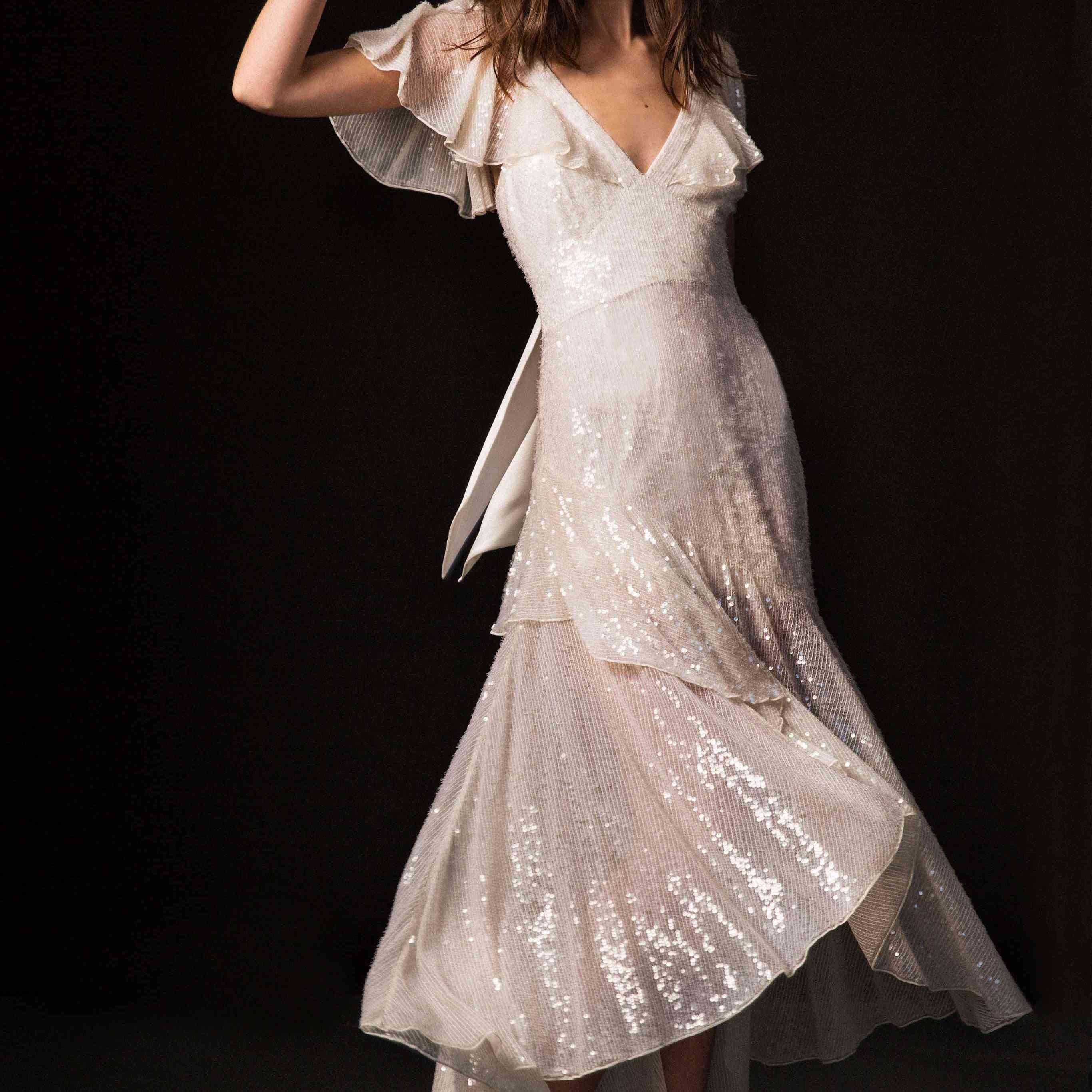Model in sequined gown with a V neck, flutter sleeves, and asymmetrical hemline