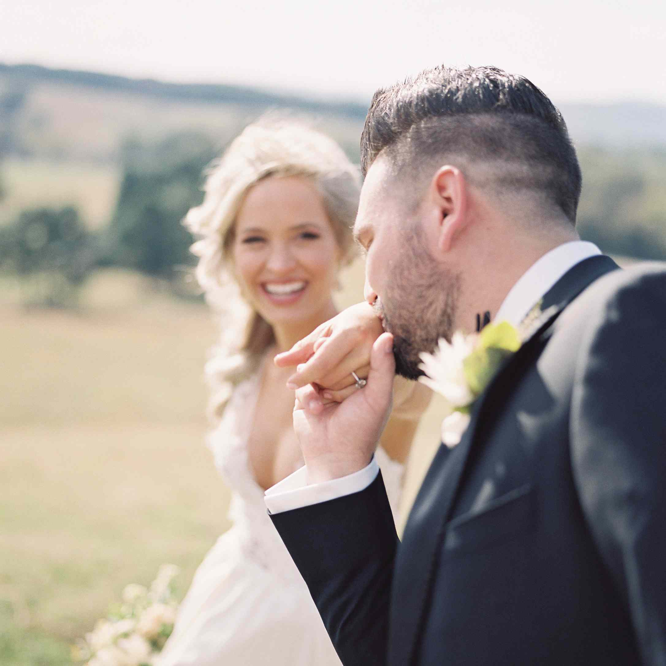 <p>Groom kissing brides hand</p><br><br>